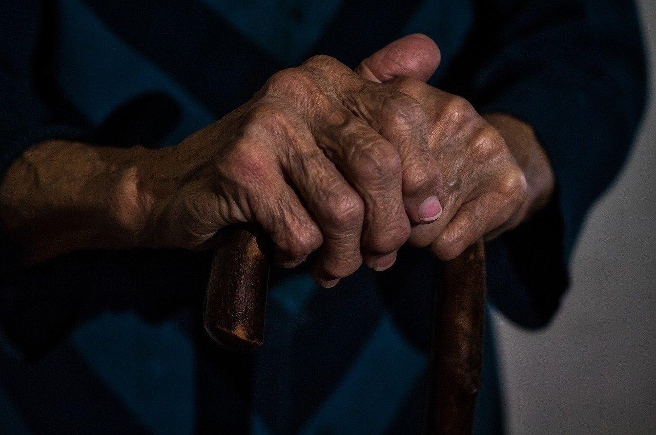 Ręce starszej osoby trzymającej laskę.